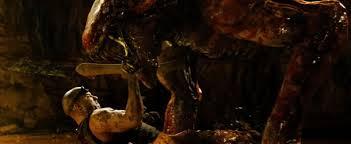 Riddick (Vin Diesel) disembowels an alien T-Rex.