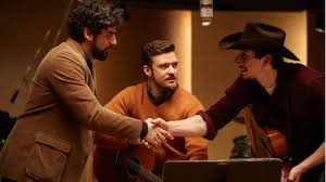 "Llewyn Davis (Oscar Isaac) congratulates Al Cody (Adam Driver) after fulfilling their lifelong dream of meeting that ""Motherlover"" guy."